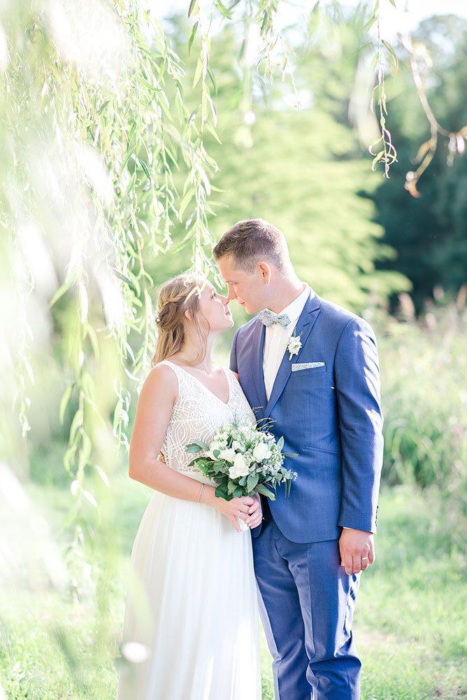 Couple de mariés devant un saule pleureur