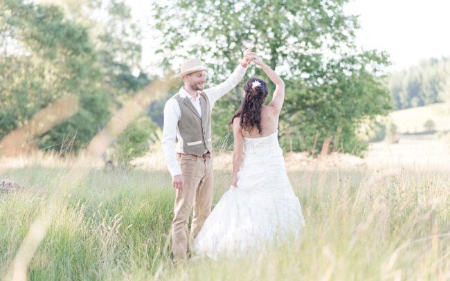 Couple de mariés en train de danser dans un cadre champêtre